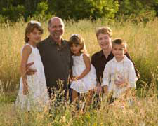Grandparents with children in a field.
