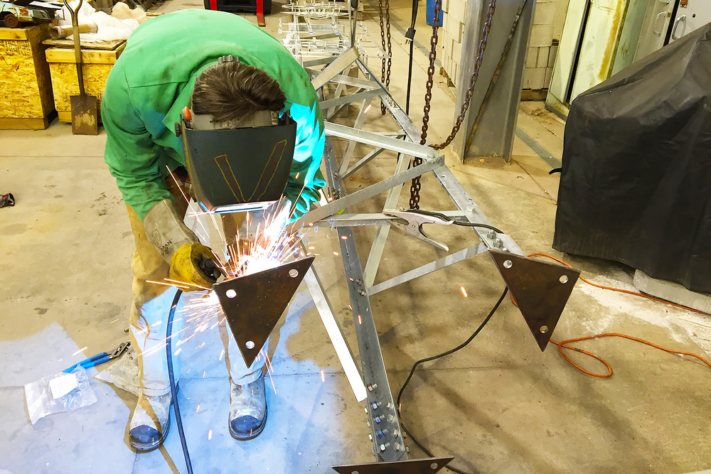 David Jones MIG welds custom mild steel feet to the tower's repurposed attachment sleeves.