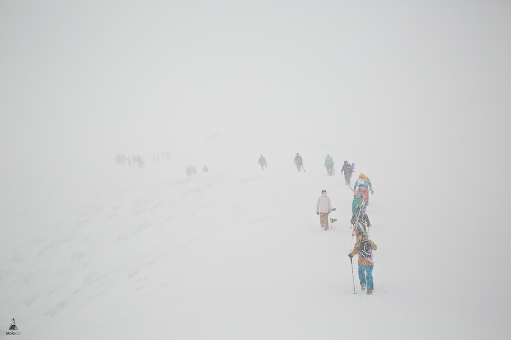 After two days of heavy snow and high winds, the summit hike at Grand Hirafu opened and a train of skiers and riders marched through the milk to access the alpine goods. March 10, 2014.