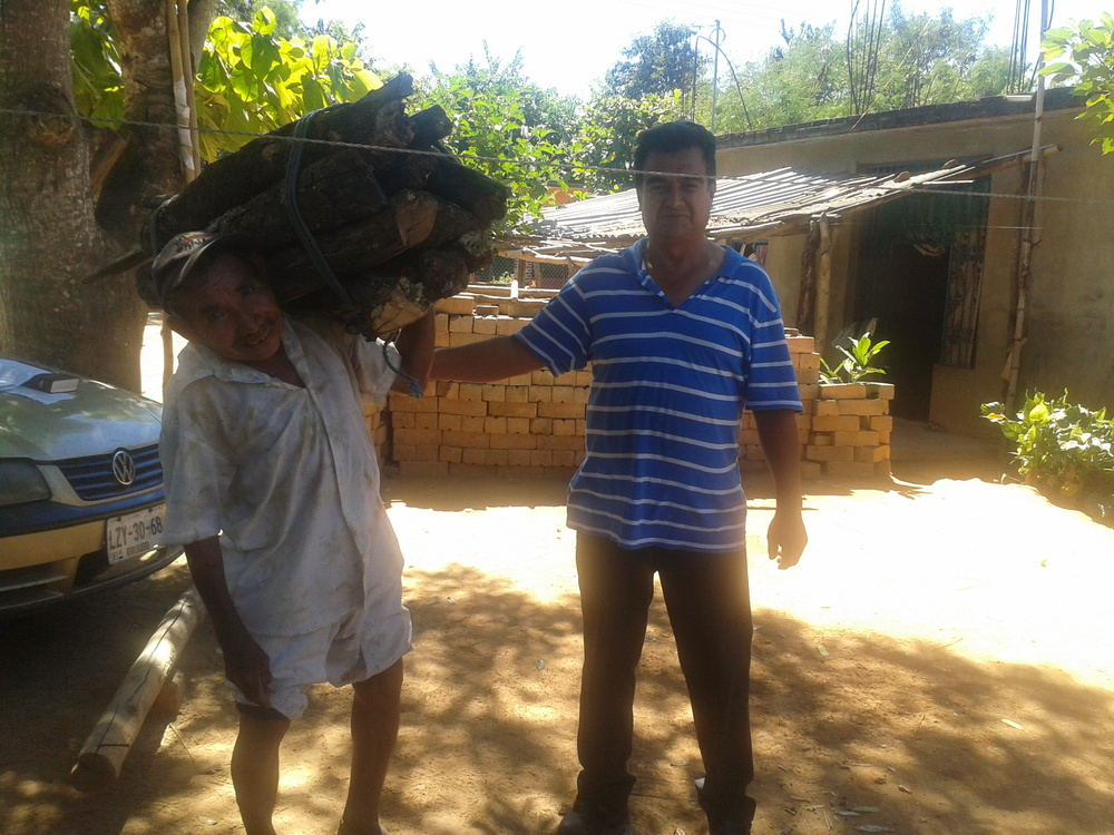 The pastor, in traditional Mixtec breeches and shirt, with Norberto, carrying firewood for cooking fires