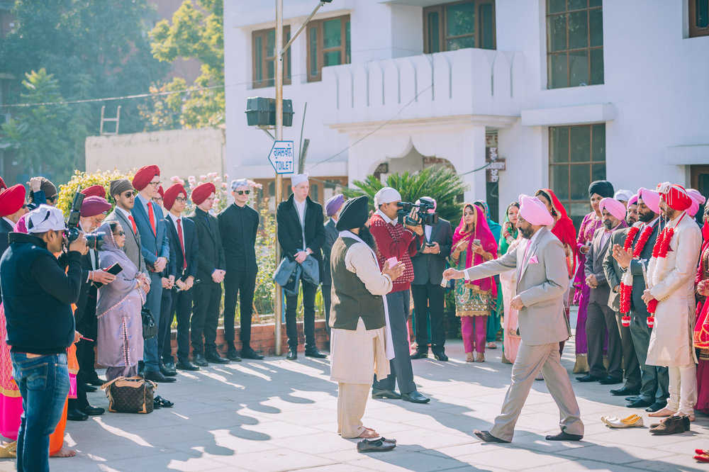 Families of the bride and groom gather for the  milni  (meeting). The priest (middle of the picture in a black turban) will then call out names of relatives from each side (beginning with the eldest) to put on a haar (garland) on each other.