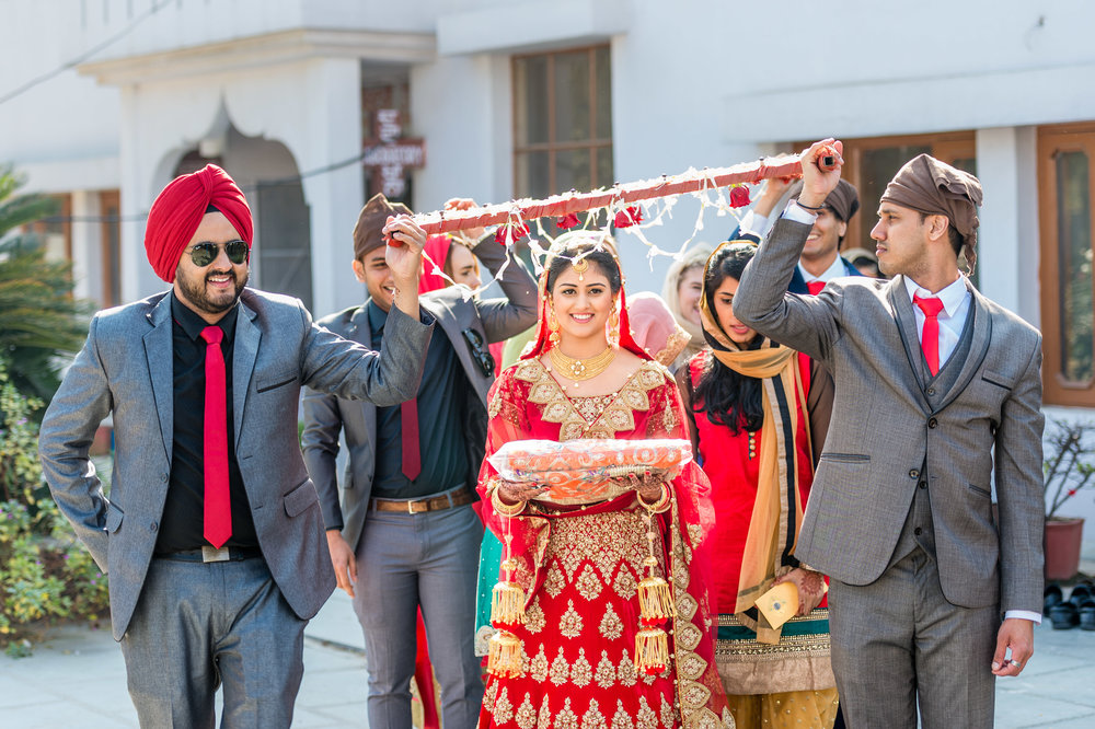 The lovely bride being escorted by her brothers into the gurdwara darbar. This is a symbolic sight because brother in the Indian culture are considered as protectors.