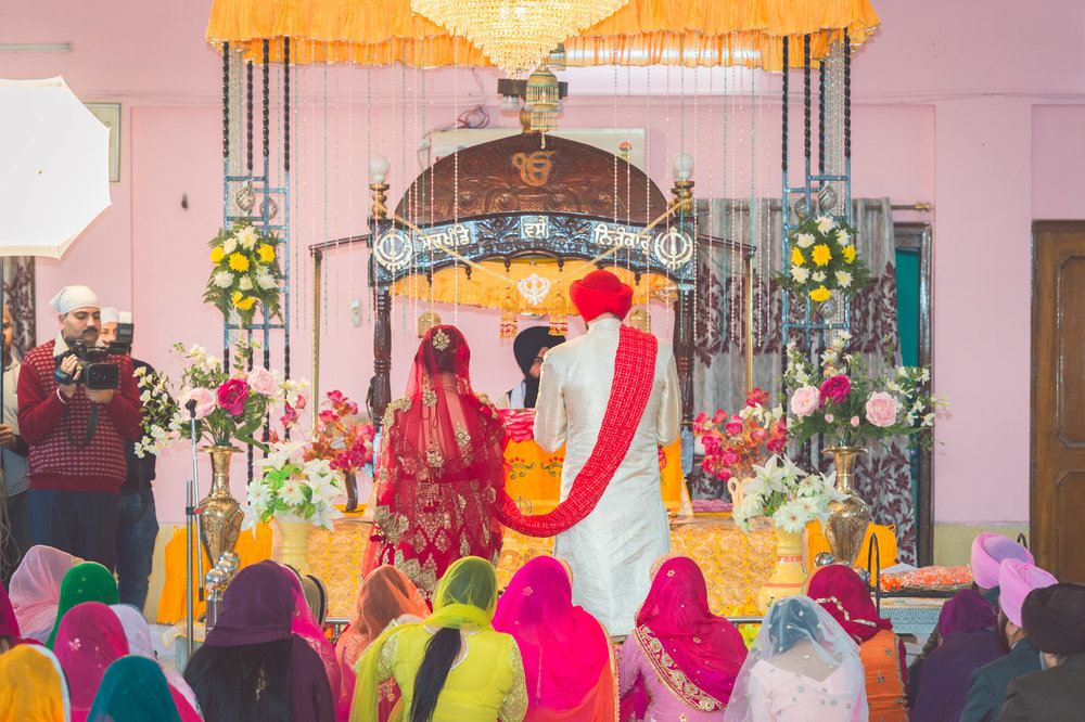 Bride and Groom standing in-front of the altar. The red scarf that is draped down the shoulders of the groom is called a  palla . It's the link between the couple as they journey around the altar.