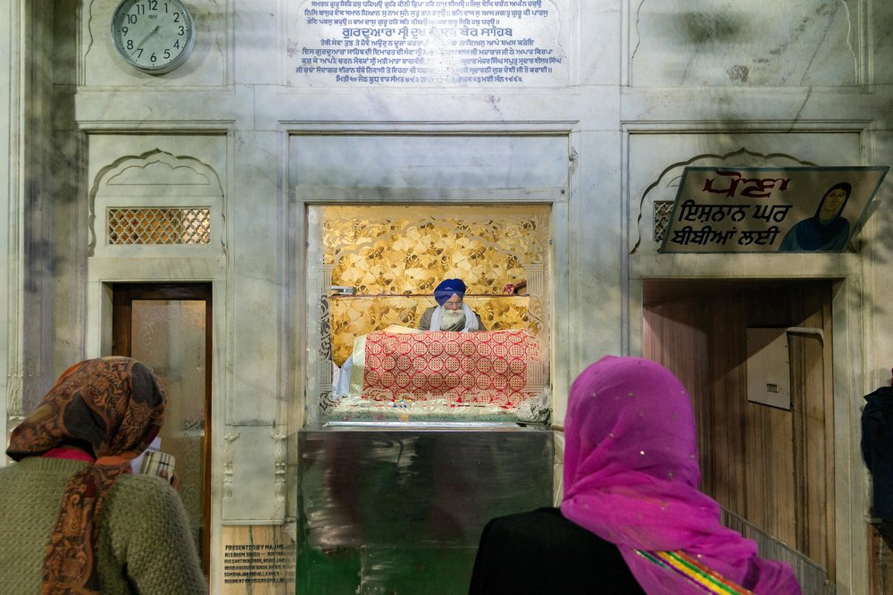 Here, you can see a priest reading text from the Holy Book (Guru Granth Sahib).