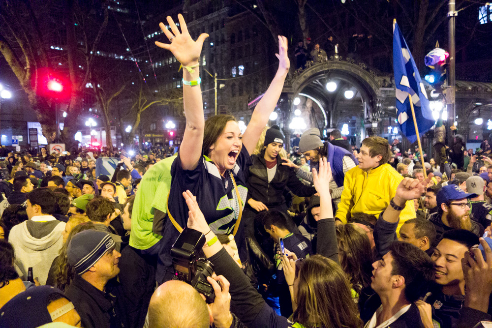 A Seahawks fan celebrates the Super Bowl win among a growing crowd in Pioneer Square.