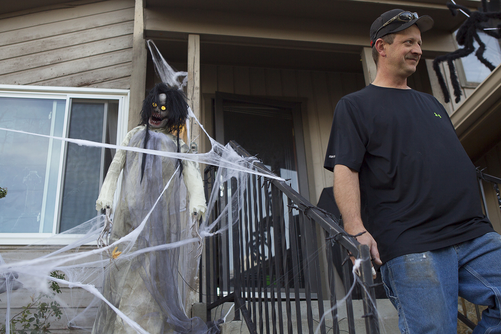 Richard Larson works Monday evening to set up his Halloween decorations. Larson says that since Halloween is the only holiday he likes to celebrate he might as well go all out.