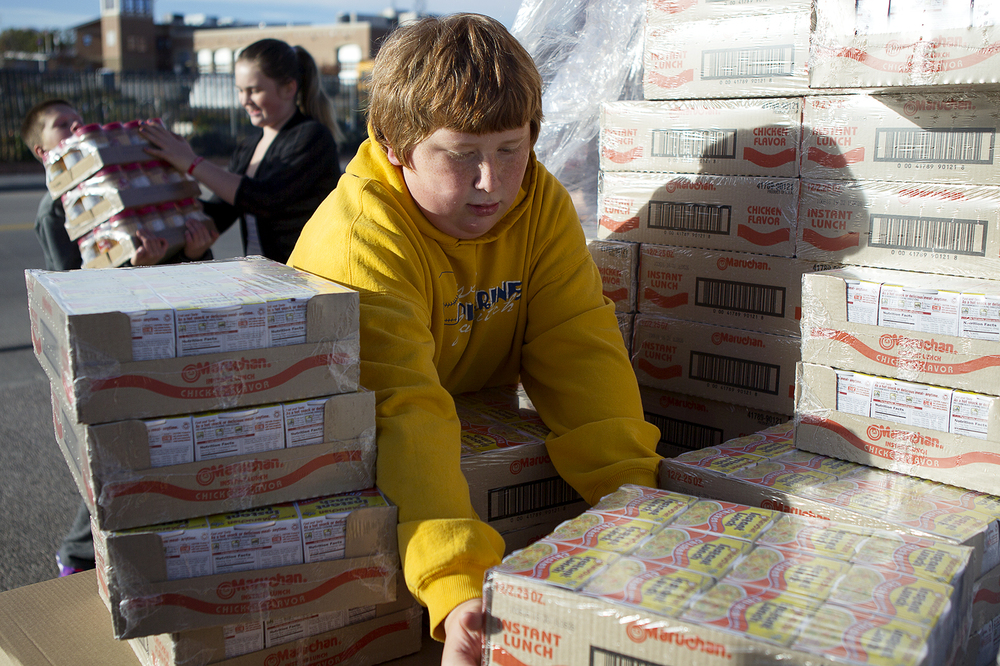 William Matthiessen, 12, helps unload food for Blessings in a Backpack. Matthiessen and his sixth grade class at Meadowlark Elementary School unloaded and organized food to be packed into backpacks and distributed at the warehouse on West First Street.