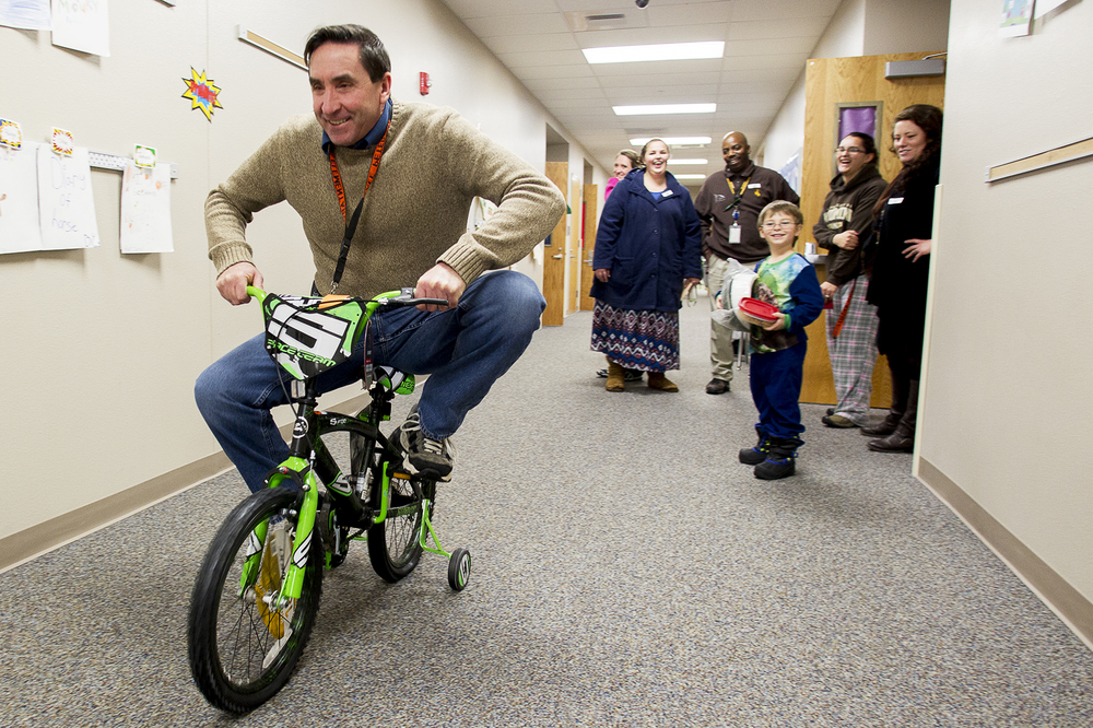 Lakeview principal Dale Petersen rides Zeke Williams's new bike down the hallway on December 22. The bike was donated to Williams by the YES House who worked with local businesses to give away 74 new bikes to children around Gillette.