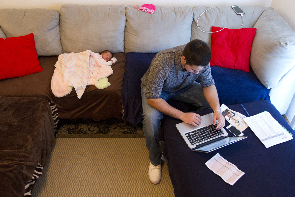 "Spencer Garcia looks for work through an online job search website while his newborn daughter Devyn sleeps beside him in their apartment in Gillette on March 1, 2016. Garcia was laid off from a temp job as a haul truck driver at North Rochelle Antelope Mine, his last day of work came about a month after signing a 12-month lease for the apartment and just days after the birth of his daughter. ""It hit me hard when I first got the news,"" said Spencer, ""(Kayla) was pregnant, I had just signed the lease. I was pretty sour about it"""
