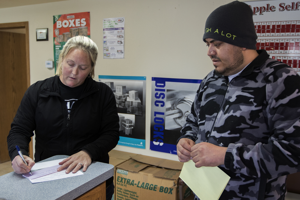 "Owner Kristene Partlow fills out paperwork for a storage unit rental for Alferdo Olveda at KP Management on March 25, 2016. According to Partlow, Olveda wasn't able to get a U-Haul truck and instead had to rent a storage unit to store his stuff while he moves to Colorado. Olveda, a drywall contractor, said his work has been steady but for ""a lot of people I know, it's pretty slow"" he said. Partlow is renting out more storage units and U-Hauls than usual as more and more people leave the region to find new work."