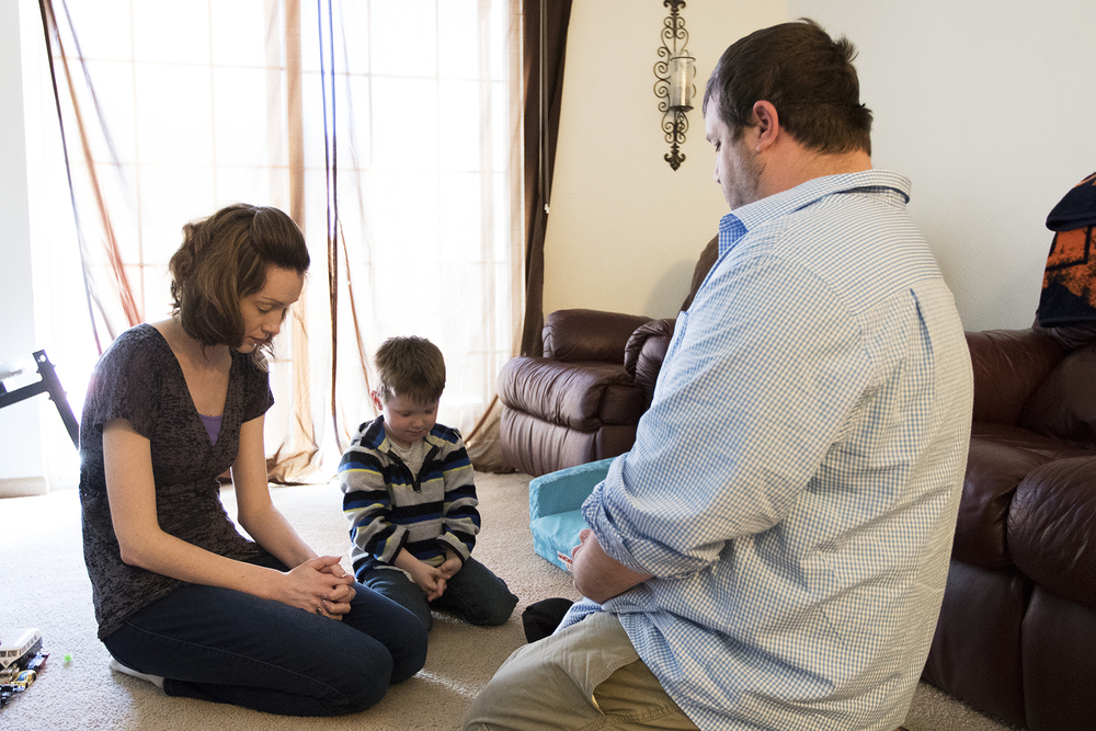 Shauna, 4-year-old Jacob and Kuillin Orcutt pray before eating lunch on Saturday April 2, 2016 at their apartment in Gillette. Kuillin, who led the family in prayer, asked for help through this tough time as he begins looking for new work after being laid off from the North Antelope Rochelle mine on Thursday.