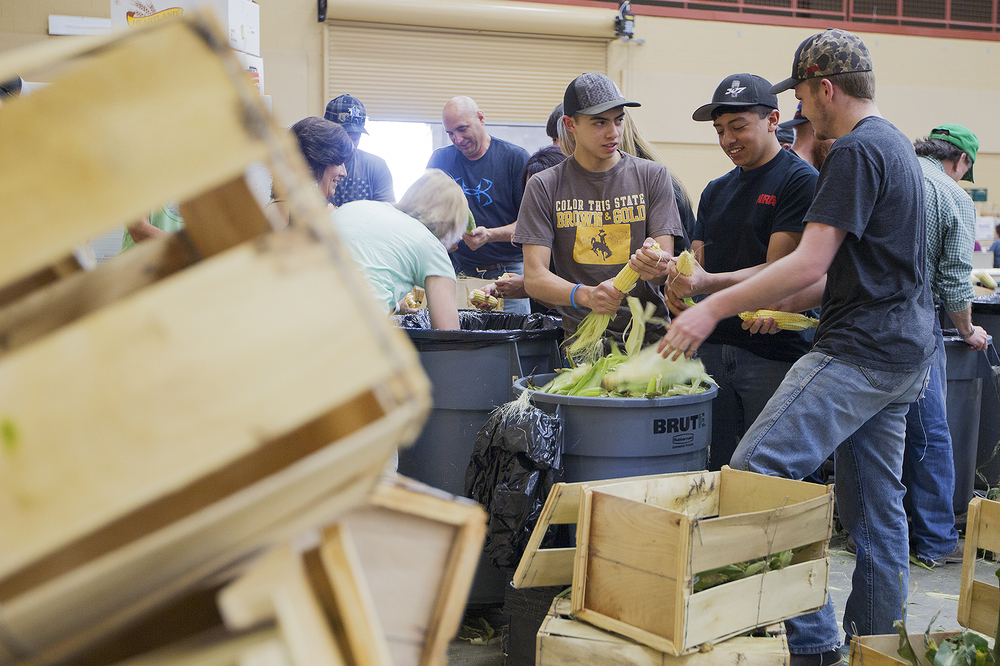 Logan Lampman, 15, from left, Luke Lampman, 18, and Josh Campbell , 17, help shuck corn Friday evening in preparation for the 33rd annual Society of Petroleum Engineers' crawfish boil at the Cam-plex Wyoming Center.
