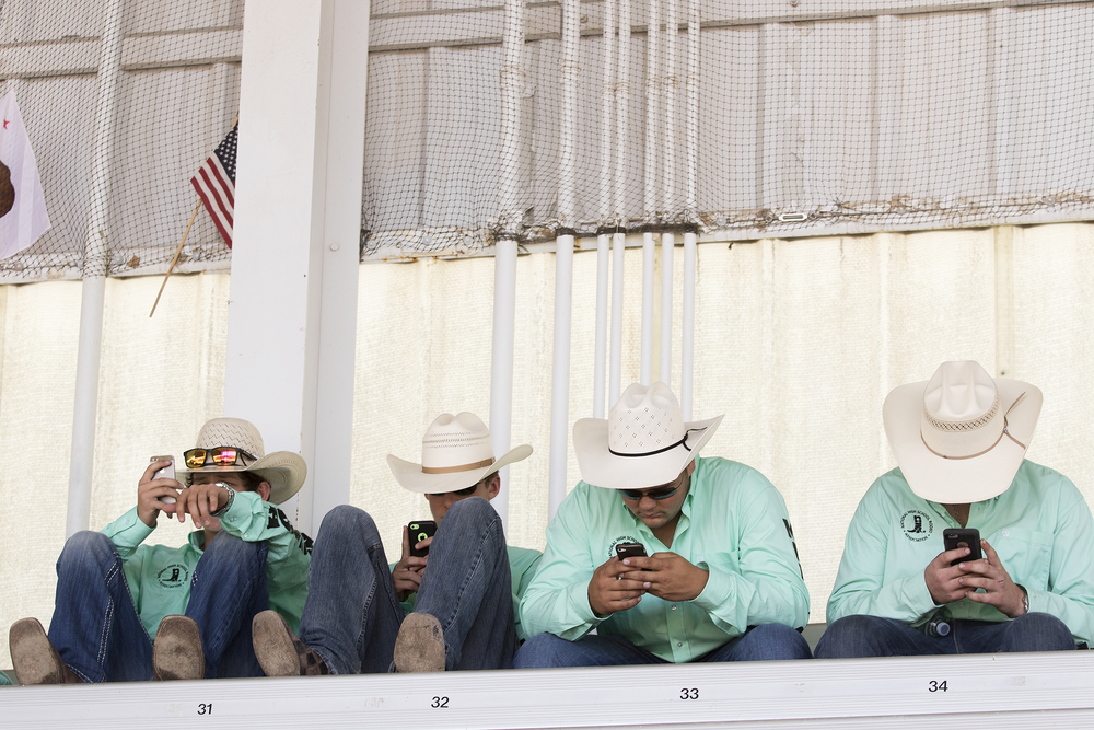 Contestants use their phones while waiting for the start of the mandatory meeting Sunday morning at Morningside Park.