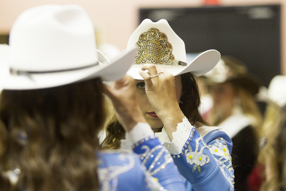 Alaska High School Rodeo Association Queen, and 2016 NHSFR queen contestant Lauren Allen checks herself in the mirror before the modeling and speeches portion of the event at the Heritage Center at Cam-plex Saturday night.