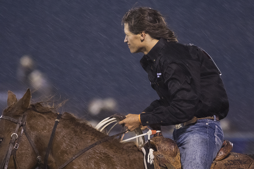 Keenan Kvamme of Carrington, N.D., rides away in the rain after after failing to record a time in tie-down roping Sunday night during the first performance of the National High School Finals Rodeo.