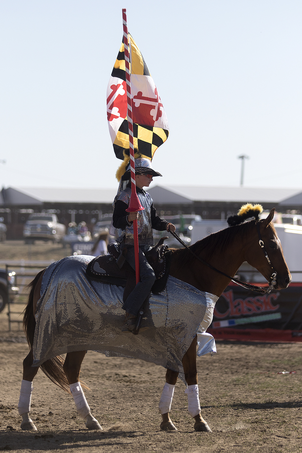 Brittany Coldiron of Team Maryland rides dressed as a knight ready for a jousting match while carrying the flag for Maryland before the Wednesday morning performance of the 2016 National High School Finals Rodeo.