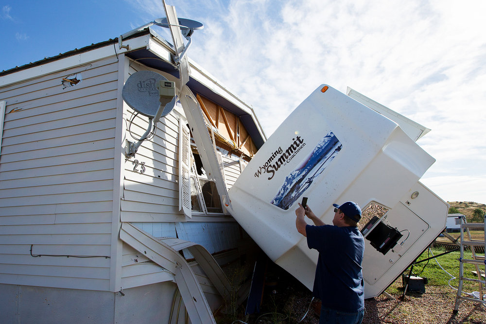 Mike Rogers takes photos of the damage to his house and his RV Friday morning in Freedom Hills East of Gillette. A storm passed over the area at about 8 p.m. Sunday evening and lifted the 12,000 pound trailer off the ground and threw it into the home.