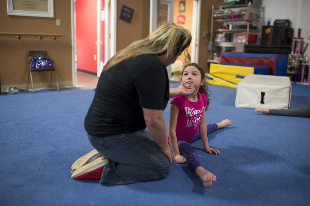 """Tammy Lockridge, 44, comforts Gracyn Traylor, 6, during practice at TK's Gymnastics in Mt. Sterling, Kentucky on Tuesday October 23, 2018. Tammy has been teaching gymnastics since she was a teenager and has been running TK's for 16 years. """"She loves these kids so much,"""" says Erin Donaldson, a coach at TK's. """"She tells 'em she loves 'em all the time."""""""