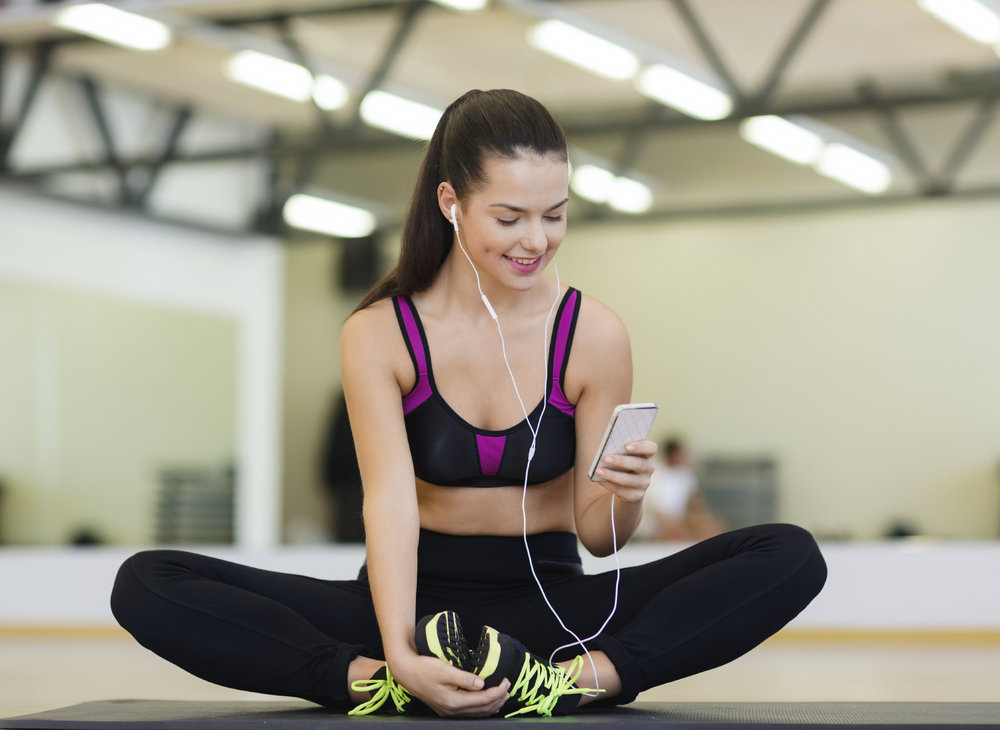 smiling woman stretching on mat in the gym