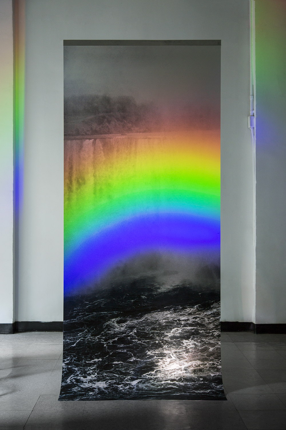 "David Chan   ""Somewhere Else""/ Inkjet print hanging from ceiling, rainbow projection using flashlight and dvd / 40"" x 96"""