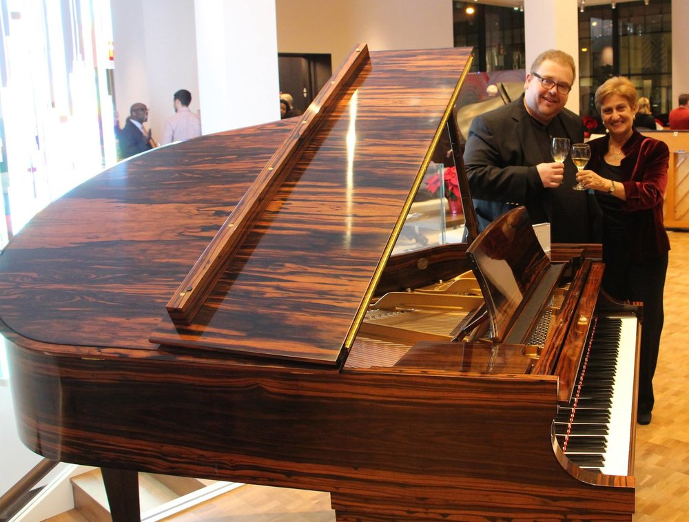 MEANYC member Alan Nunez and President Barbara Novick toast amongst the beautiful Steinway grands.