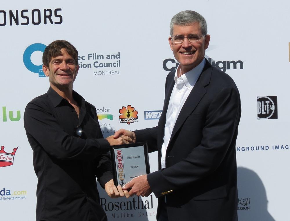 """スチュウ・リービー(左)が映画プロジェクト"""" COLUSA """"で2位を獲得したノーム / ハンターに賞を授与しているところ"""