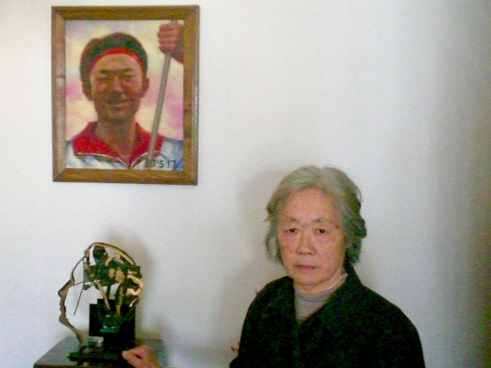 Ding Zilin in front of a portrait of her son Jiang Jielian. (C) Remko Tanis