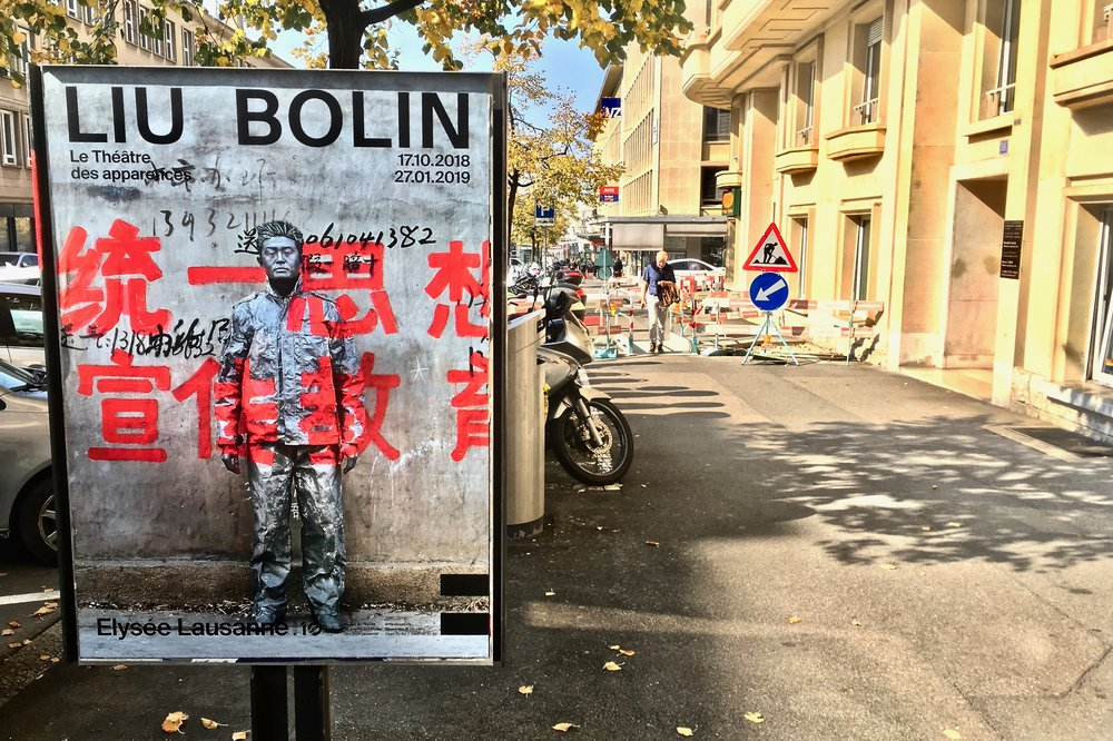 Poster for Liu Bolin's 2018 exhibition at the Elysée Museum in Lausanne, Switzerland. (C) Remko Tanis
