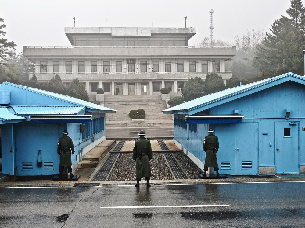 South Korean soldiers at the DMZ looking across the border towards a North Korean soldier on guard. (C) Remko Tanis