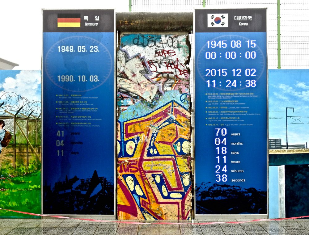 Signs at Dorasan train station in northern South Korea: left stating how long East and West Germany were separated, right digitally continuing to count the duration of the Korean division. In between the signs an original piece of the Berlin Wall. Photo: (C) Remko Tanis