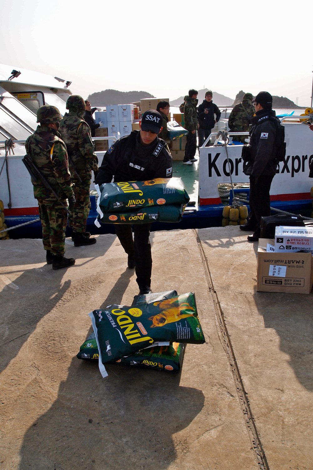 South Korean military personnel off loading dog food from a ferry at Yeonpyeong Island, which was evacuated after being hit by shelling from North Korea. (C) Remko Tanis