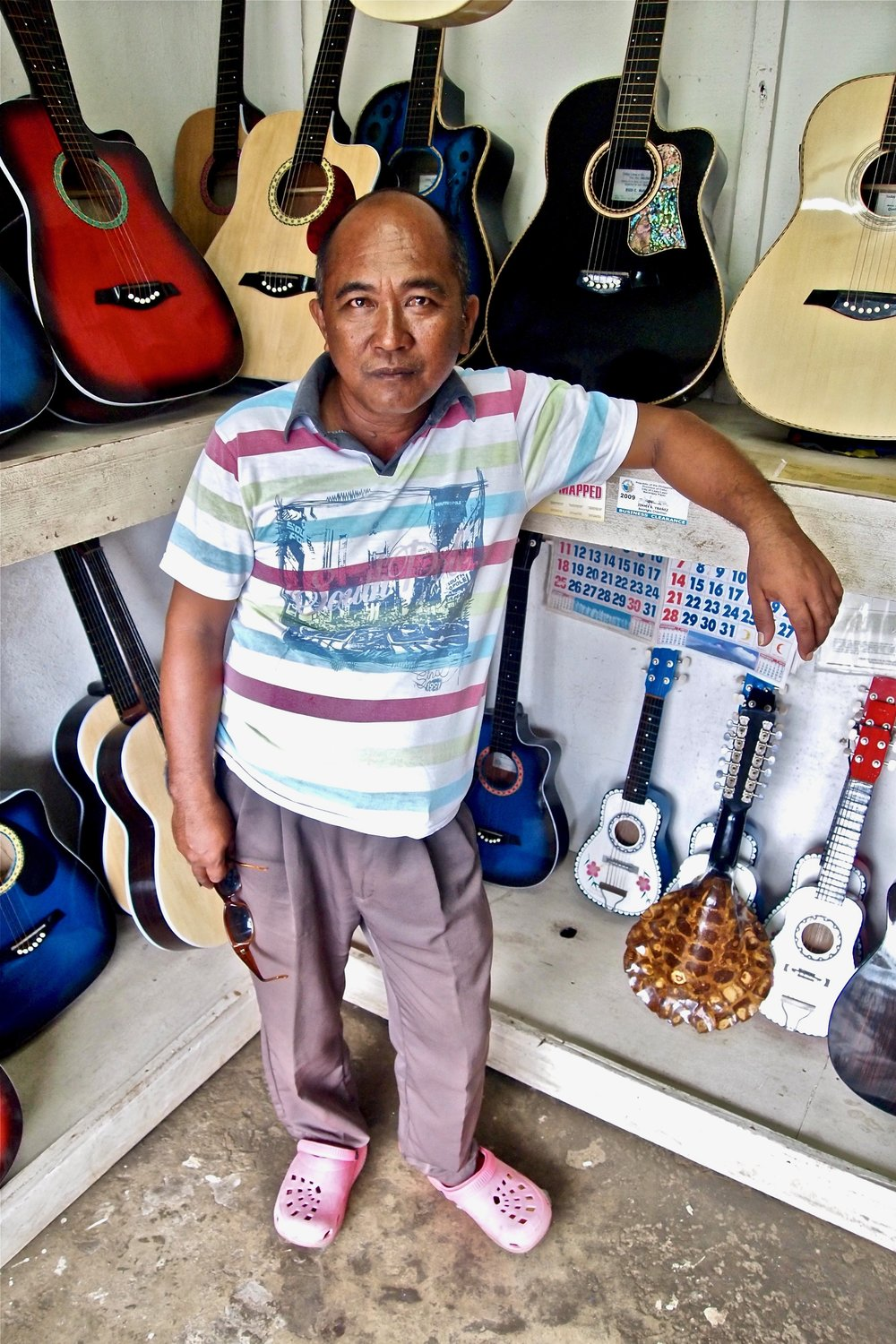 Ike Biloy in his guitar shop in Lapu-Lapu City. His eldest daughter sends money home from Japan, where she works in a bakery. (C) Remko Tanis
