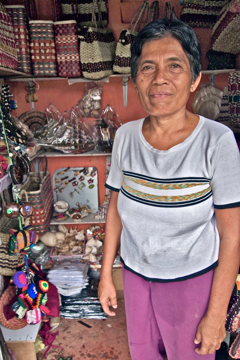 Helen Ybañez in her souvenir stall in Lapu-Lapu City, the Philippines. She is raising four grandchildren, while her son works in Saudi Arabia. (C) Remko Tanis