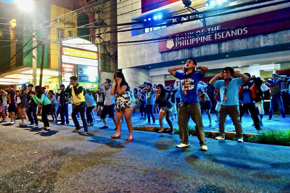 Employees of a call center dance in front of their office building to recruit new staff in Cebu, the Philippines. (C) Remko Tanis
