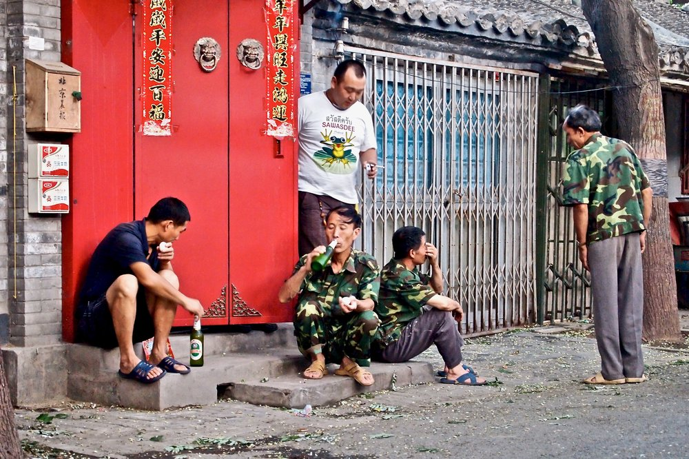 Men drinking a beer in Beijing, China. (C) Remko Tanis