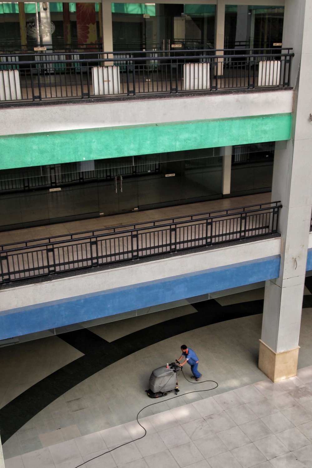 A cleaner at work in the empty New South China Mall in Dongguan, China. Photo: (C) Remko Tanis