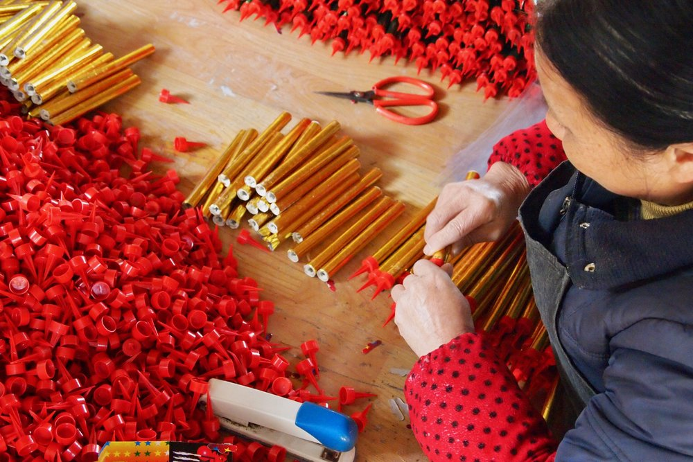 An employee putting caps on fireworks tubes at Dream Fireworks factory in Liuyang, China. Photo: (C) Remko Tanis