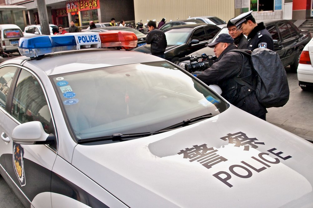 Lu Jianfu questioning a cop in an illegally parked police car in Zhengzhou, China. Photo: (C) Remko Tanis