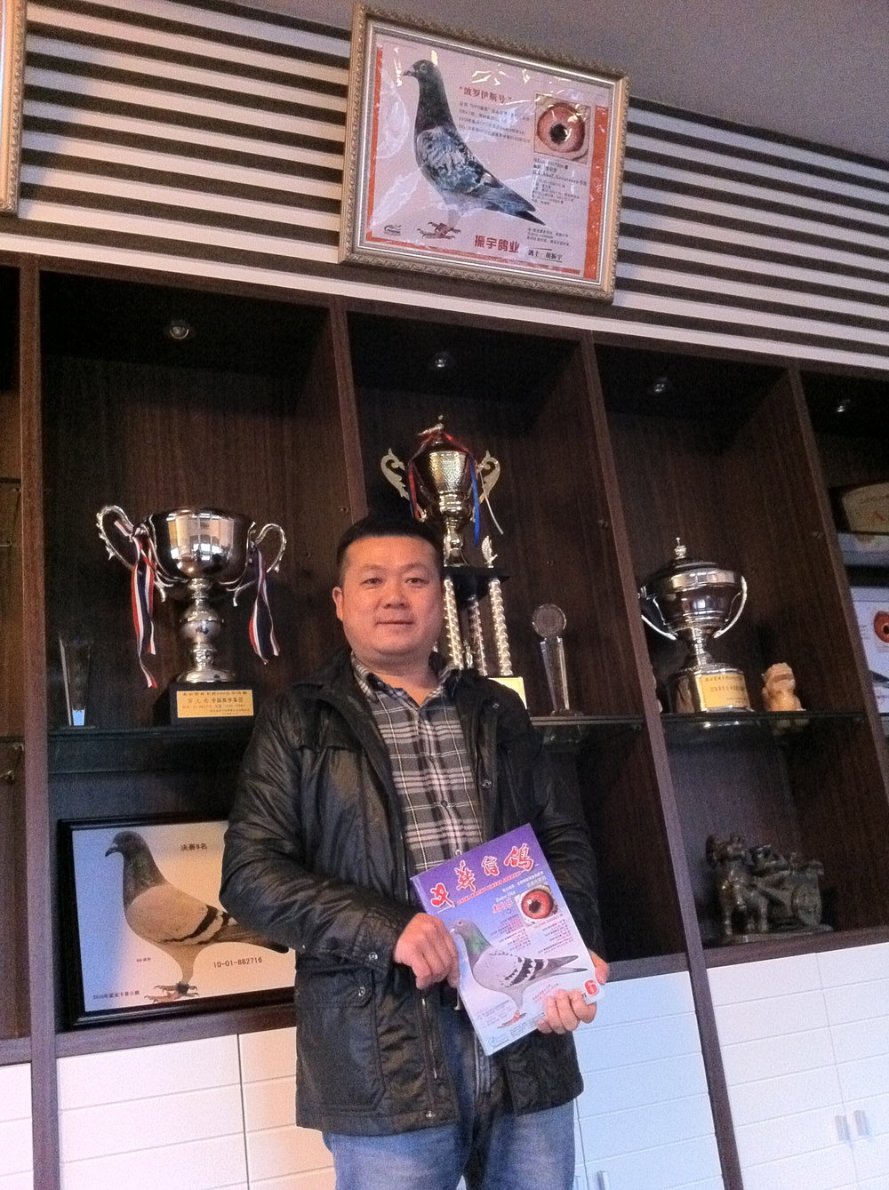 Hu Zhen Yu with pigeon Dolce Vita on the cover of the magazine, which he had just bought for a record amount. Photo: (C) Remko Tanis
