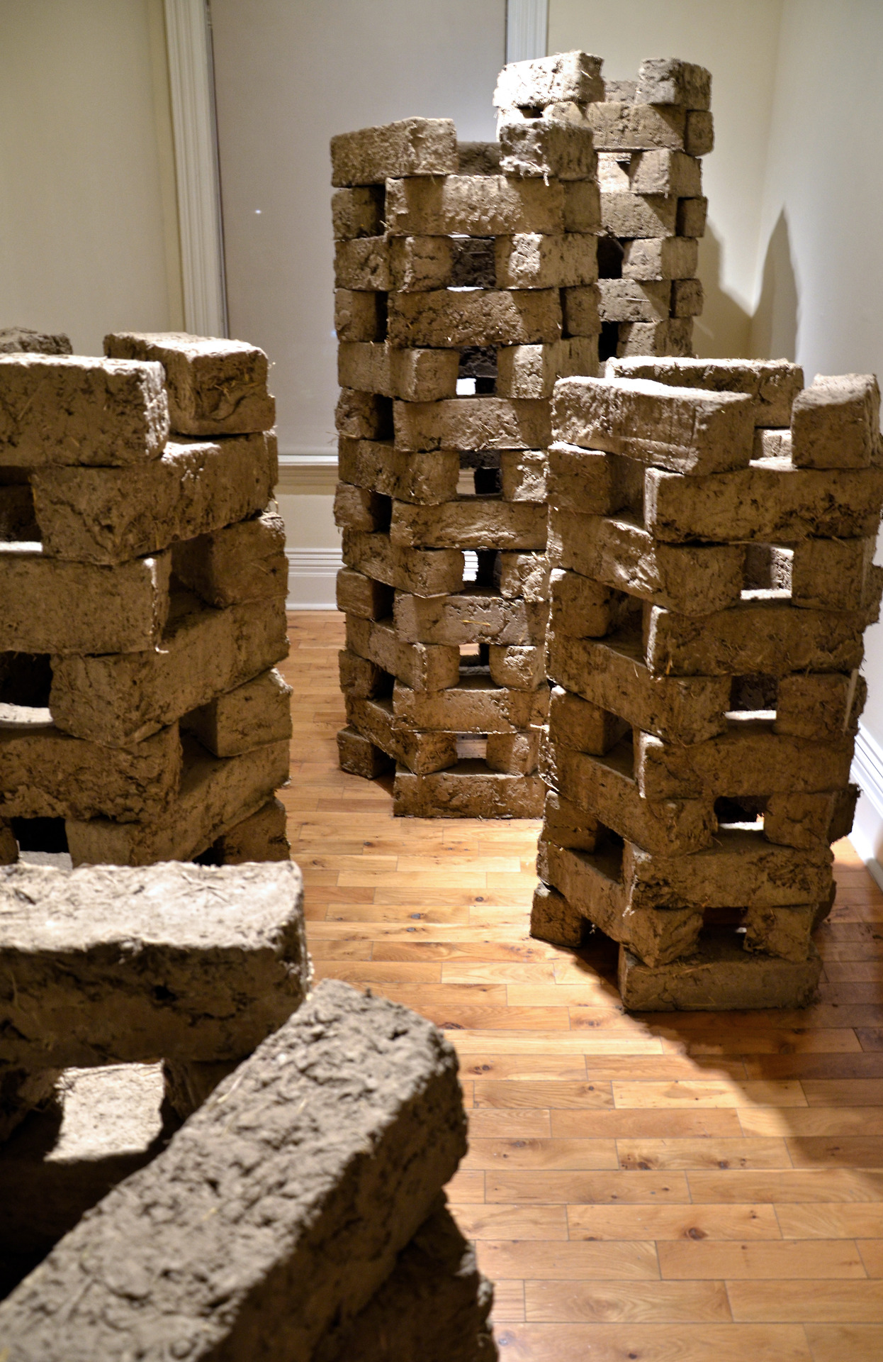 dirt. - matthew caudle + robert cram   grow op. gladstone gallery. 2013.   dirt explores constructions of the landscape or exterior as being wild, rebellious and expressive, with its counterpart, the indoors, as being obedient, organized and authoritarian.   the installation examines our accelerating ambition to bring order to complex natural systems. hand made bricks are constructed into increasingly more complex nests, a prelusive symbol of manipulation and control in the environment.
