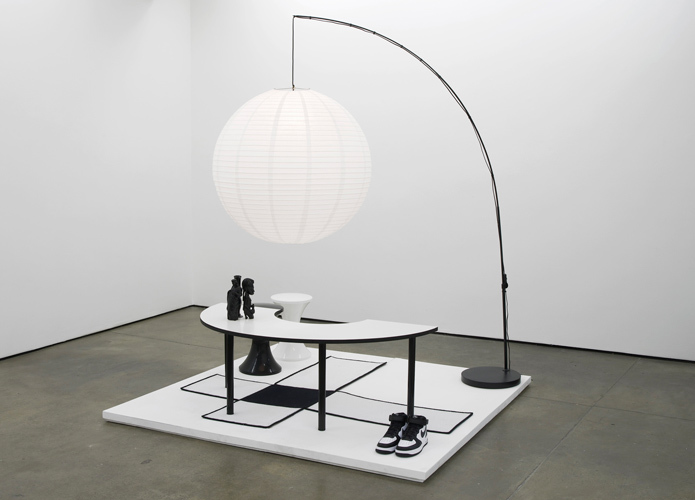 Untitled: Furniture Island No. 8 2012 Eliterank carpet, oversize Chinese Globe paper lantern, Branex Tam Tam stools, Costcutter Arc classroom table, Jesus figurine, vintage African carving, acrylic bong, Nike Air Force 1's 200 x 200 x 200 cm