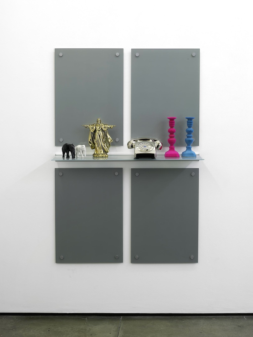 Matthew Darbyshire Untitled Homeware No. 9, 2011 Painted black and white carved elephant ornaments, chromed gold porcelain Jesus figurine, chromed silver retro telephone, flocked fuchsia brass candlestick, flocked turquoise brass candlestick, glass and steel supports: 135 x 95 x 26.5 cm