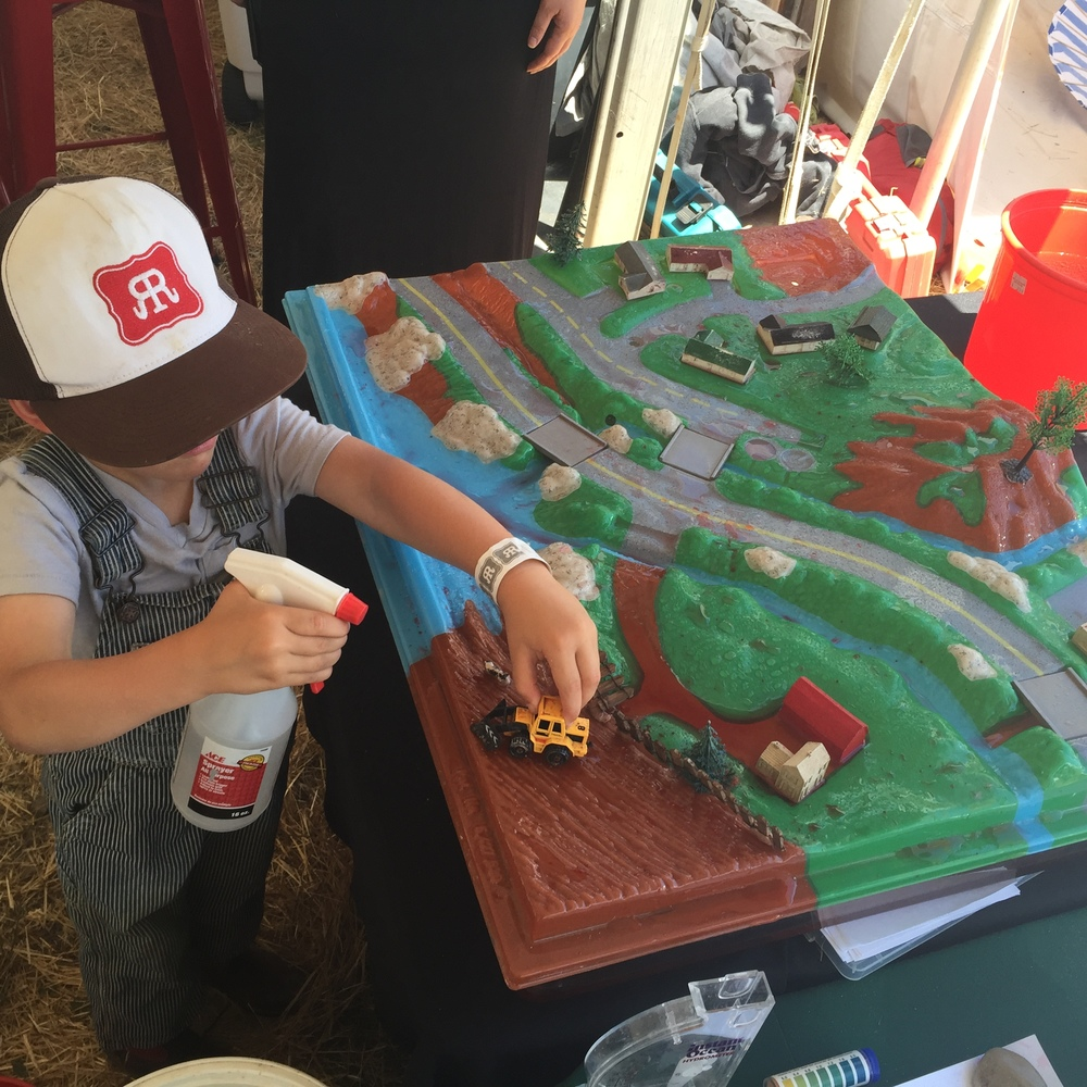 A young Rivertown Revival go-er learns how pollutants travel through a watershed environment while playing with a really cool tractor.