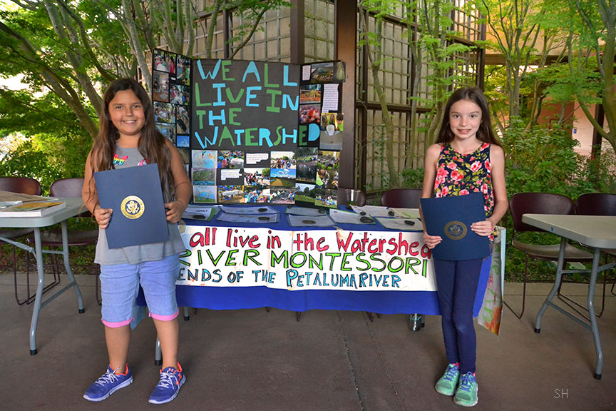 Students Jocelyn Edwards and Sara Christmann Rigsby of River Montessori Charter school stand with their project table after presenting.