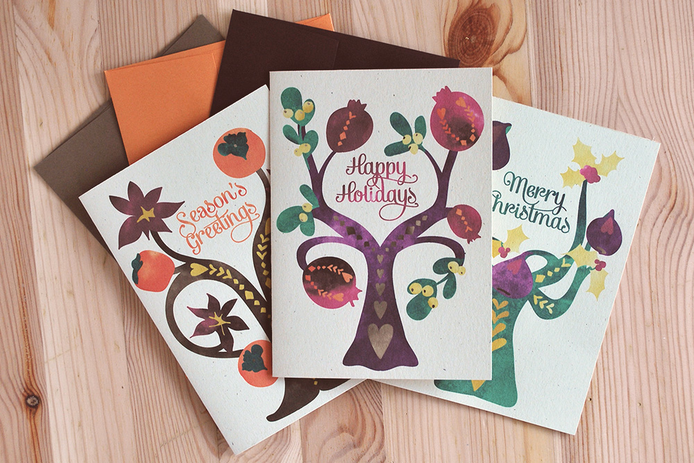 Our Folk Tree holiday cards feature original watercolor artwork flat printed on organic husk card stock. Persimmons, pomegranates and figs dance atop folksy tree branches accompanied by star anise, mistletoe and holly.