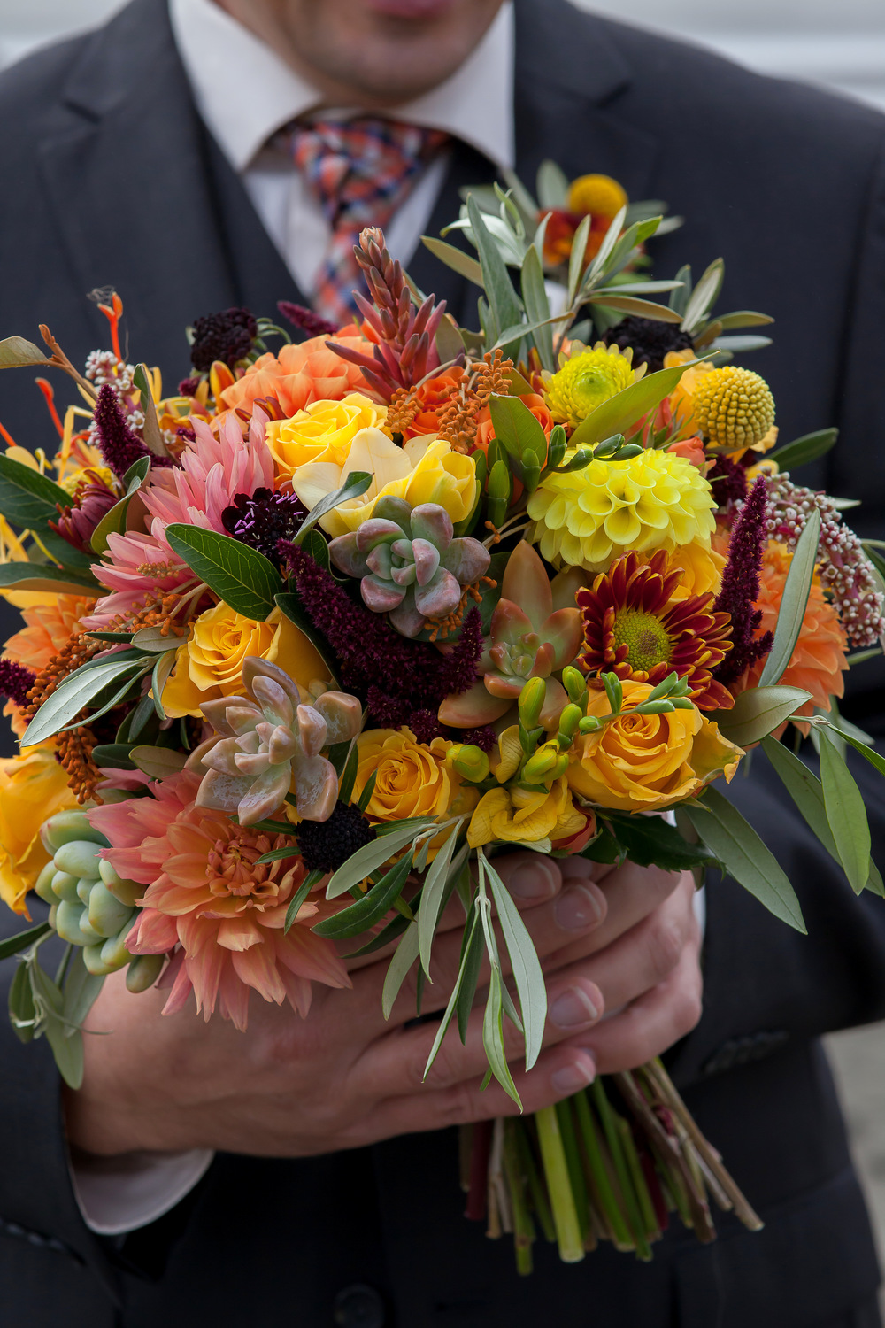 Molly's bouquet was an exuberant mix of dahlias, roses, mums, crasepdia, succulents, olive branches, ammaranth and ginger. Thank you to jjt Photography for sharing this lovely photo.