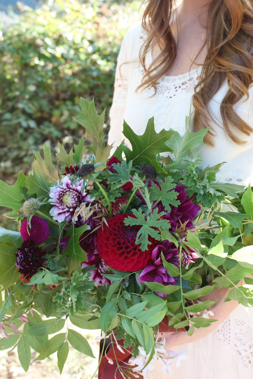 Marisa's Ranch wedding bouquet was a loose mix of all local organic blooms and foliage. Include were five different varieties of dahlias, scabiosa, pods and blooms, sweet smelling jasmine, and geranium and finished with oak leaves, Chinese pistache leaaves and grasses.