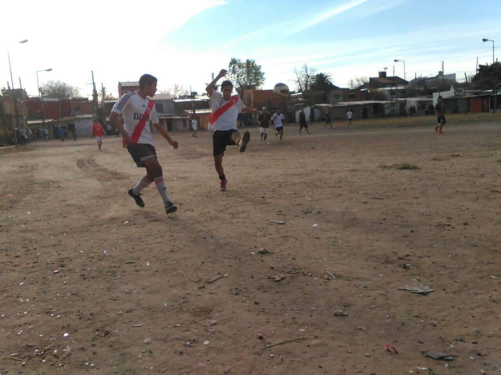 Kids playing soccer in La Cava, Argentina, site of a future safe space for soccer and community activities.