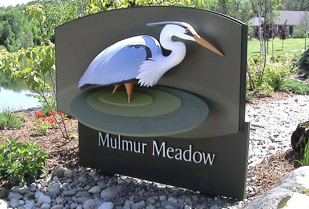 "An upscale, modern resort in a natural setting. The heron's quiet stature and the broad, stylized, rippling water evoke a sense of peace, calm and relaxation. The ""cradling"" shape of the sign relates to the curve of the nearby pond.     Sign:  80""w handcrafted HDU. Curved back and pebble textured lower panel (under Mulmur Meadow). Brushed aluminum letters."