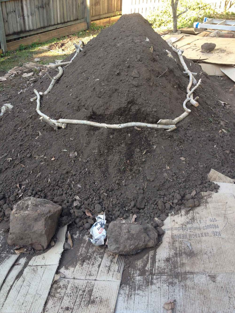 Adding the excavated soil to the mound. Branches pegged around middle-section of the mound to hold soil.